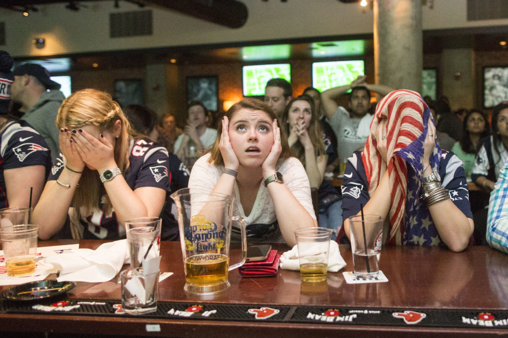 Fans watch the New England Patriots play on television in the 2015 Super Bowl. This year, the Patriots face the Atlanta Falcons.
