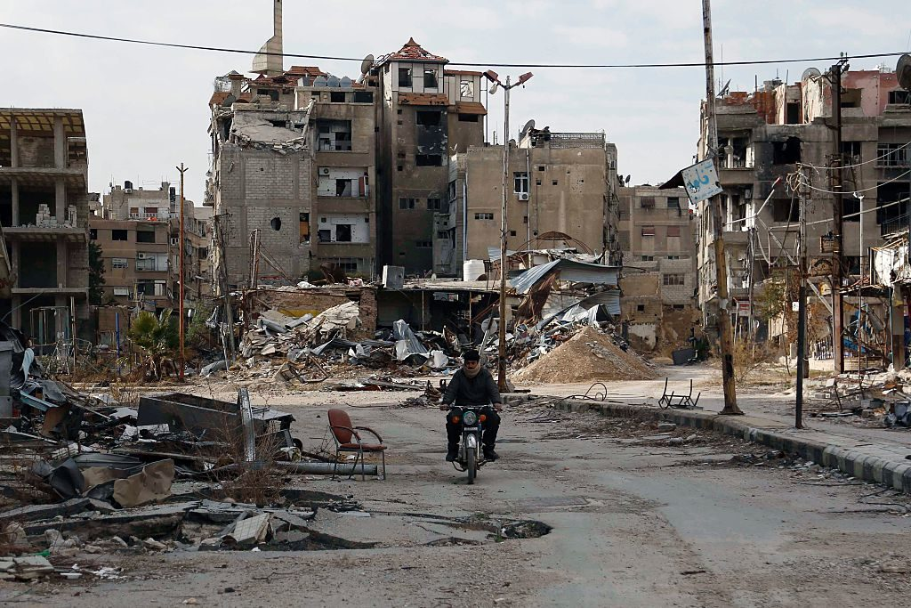 A man drives his motorbike past damaged buildings in Harasta, east of the Syrian capital Damascus, in February, 2016.