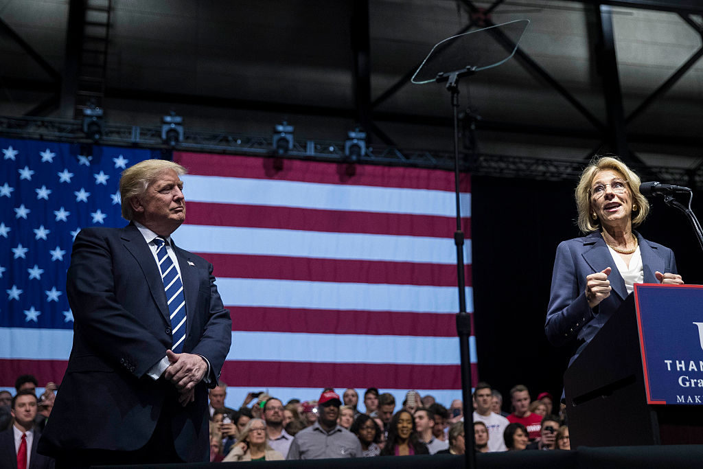 President-elect Donald Trump looks on as Betsy DeVos, his nominee for Secretary of Education, speaks in Grand Rapids, Michigan.