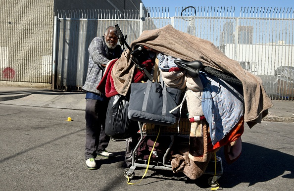 A homeless man pushes his cart of belongings along a street in Los Angeles in February 2016.