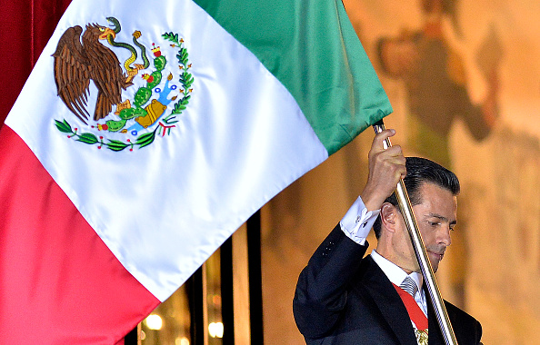 Mexican President Enrique Pena Nieto waves his country's flag on Independence Day in Mexico City on September 15, 2016.