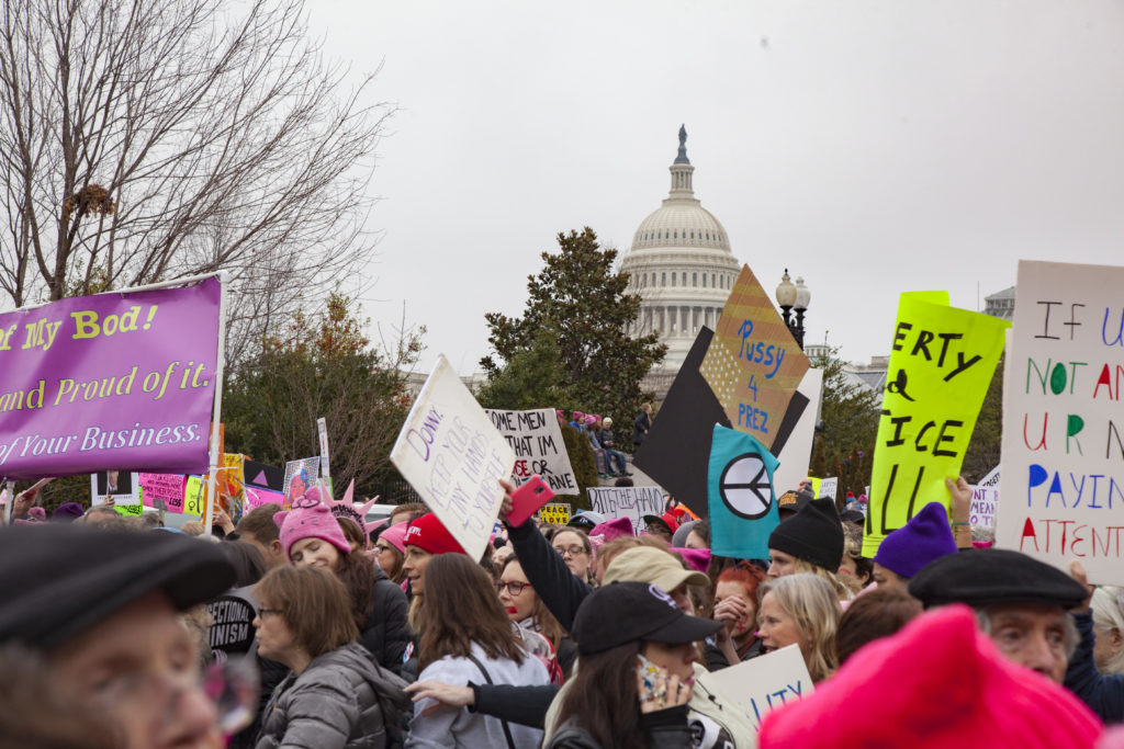 Marchers wave signs in front of the Capitol at the Women's March on Washington, one of several large protests that followed the inauguration of President Donald Trump.
