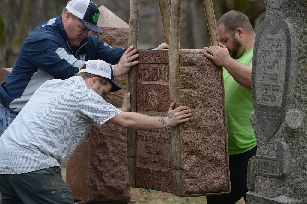 Volunteers from a local monument company help to reset vandalized headstones at Chesed Shel Emeth Cemetery on February 22 in University City, Missouri. Since the beginning of the year, there has been a nationwide spike in incidents including bomb threats at Jewish community centers and reports of anti-semitic graffiti.