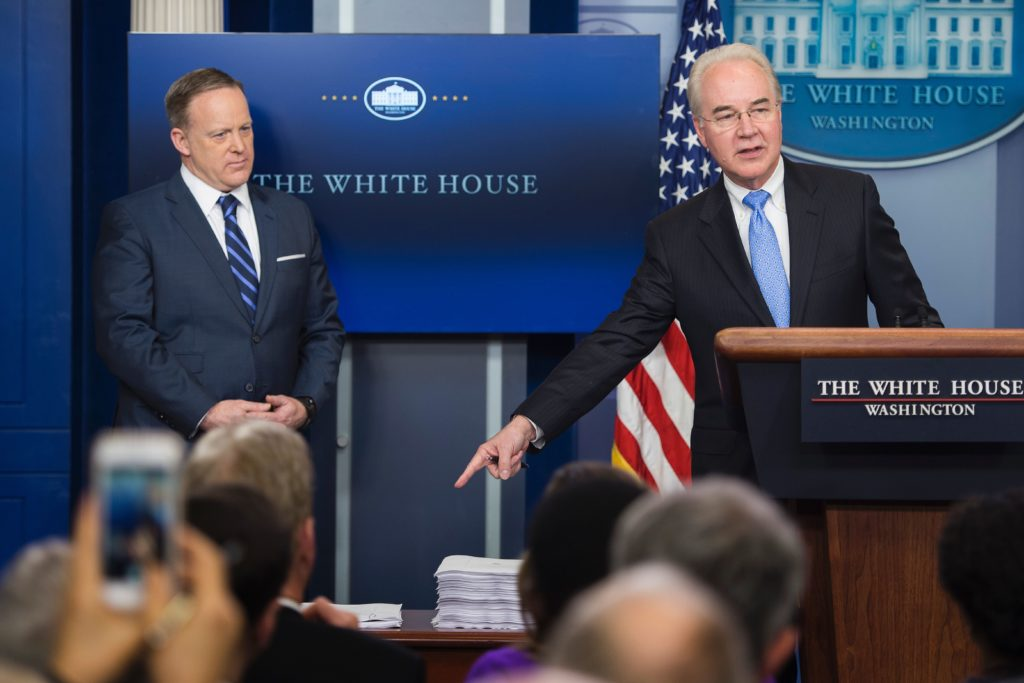 White House Press Secretary Sean Spicer (L) looks on as U.S. Secretary of Health and Human Service Tom Price (R) points to a print-out of the Affordable Care Act (ACA) and a copy of the new plan introduced to repeal and replace the ACA during the daily briefing at the White House.