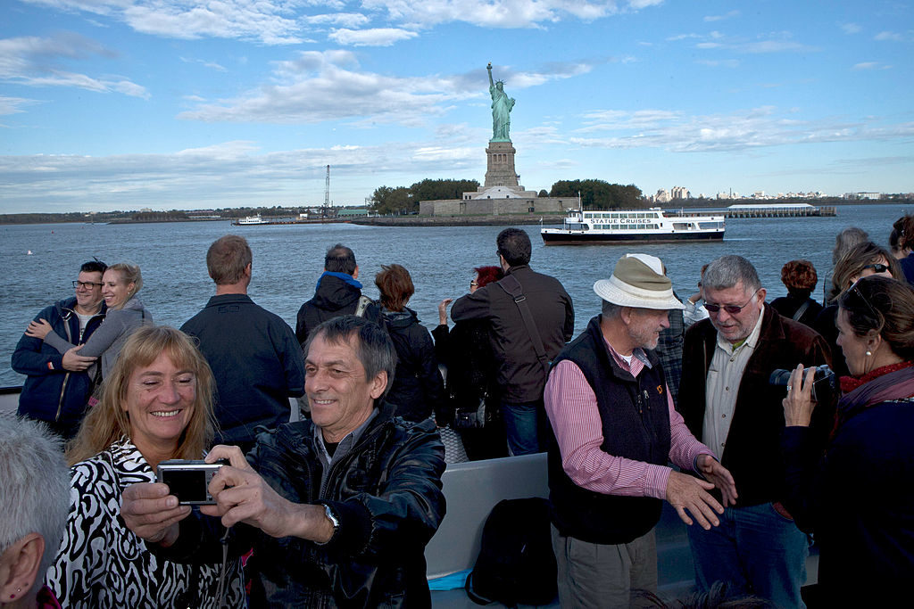 A group of tourists take and pose for photographs as they pass near the Statue of Liberty. The U.S. Travel Association says there's been a slump in tourism to the U.S. recently.