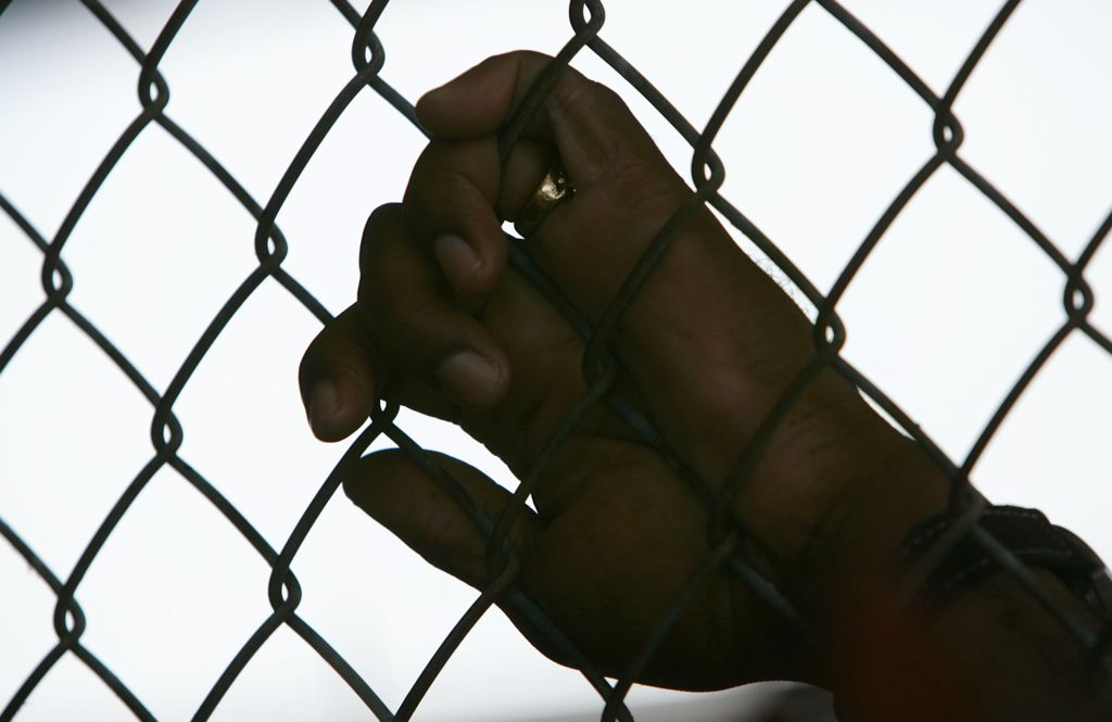 An inmate holds onto a fence at Angola Prison in Louisiana.