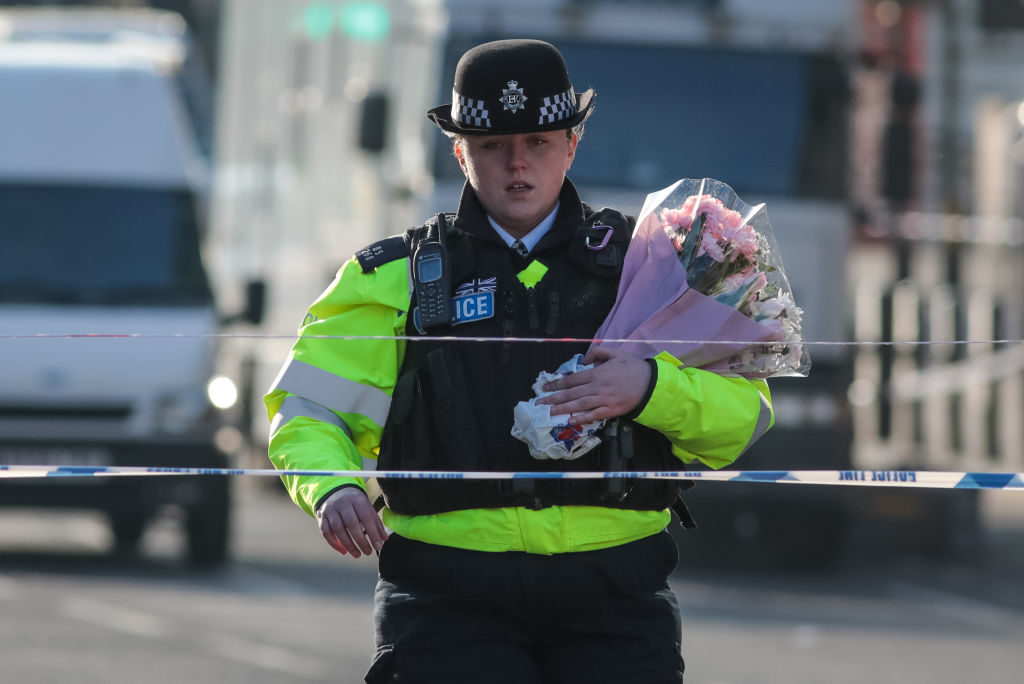 A police officer arrives with floral tributes on Westminster Bridge in London following Wednesday's attack in which one police officer was killed.