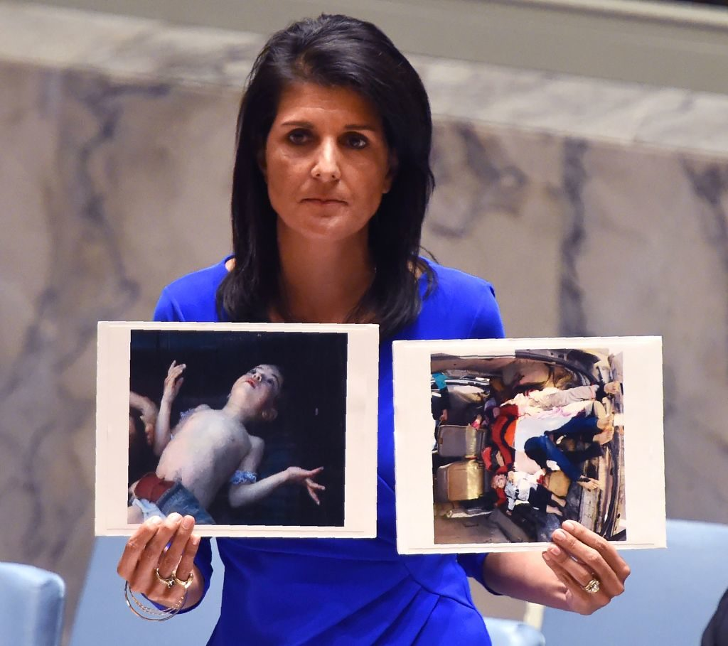 US Ambassador to the UN, Nikki Haley, holds photos of victims as she speaks as the UN Security Council meets in an emergency session at the UN on April 5, 2017, about the suspected deadly chemical attack that killed civilians, including children, in Syria.