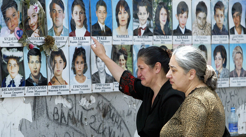 Women cry near children's pictures in the destroyed school sport hall in Beslan, Russia, where more than 330 hostages were killed in a siege by Chechen militants in 2004. In a ruling this week, the European Court of Human Rights criticized the Russian government for failing to do more to try to stop the massacre.