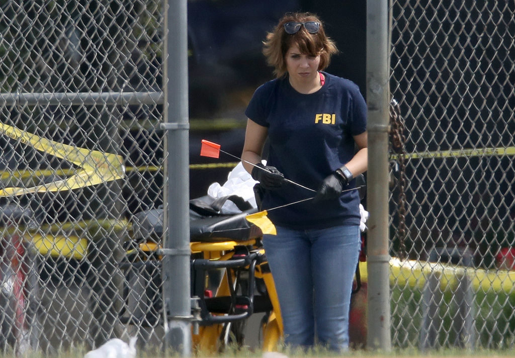 An FBI investigator uses evidence flags to mark the location of items found at Alexandria, Virginia's Eugene Simpson Field, where a gunman opened fire on Republicans practicing for a charity baseball game.  House Republican Whip Steve Scalise (R-LA) was among those injured in the shooting.