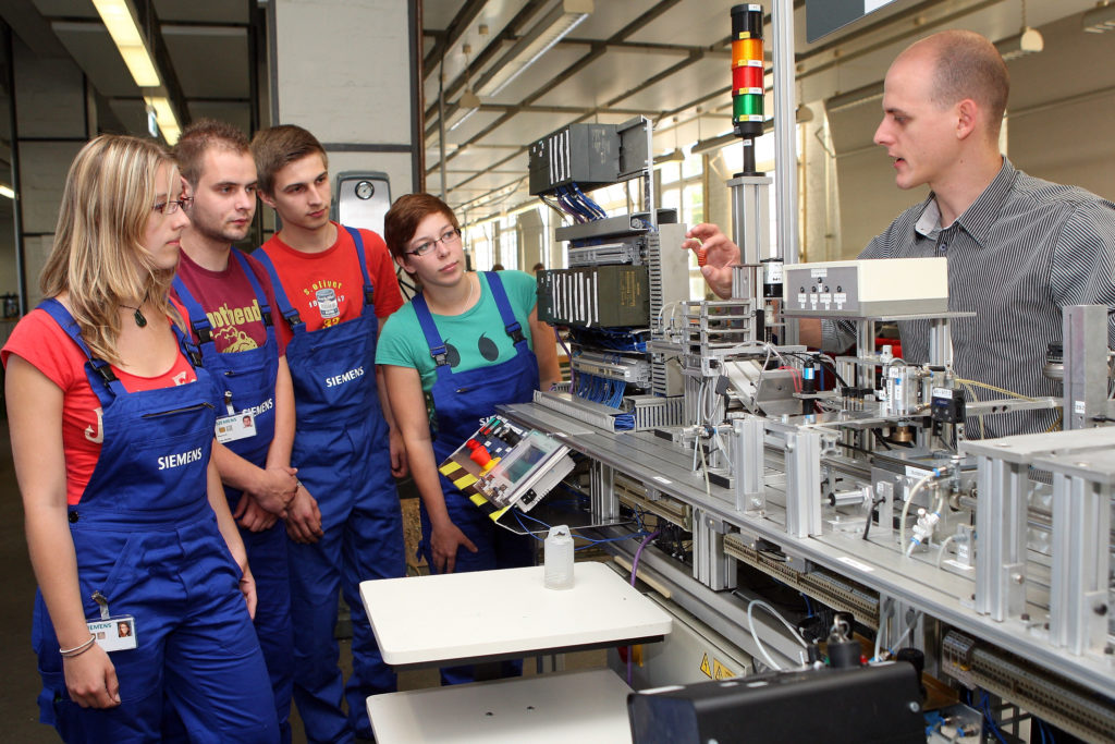 An instructor at the Siemens training center in Berlin, Germany with apprentices.  In Germany, apprenticeship training is much more common than in the United States.