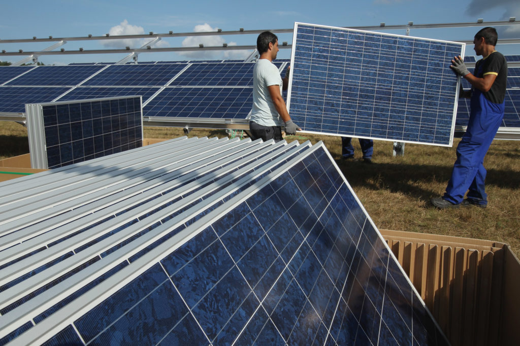 Workers install solar panels containing photovoltaic cells near Muencheberg, Germany. Could the U.S. make similar investments?