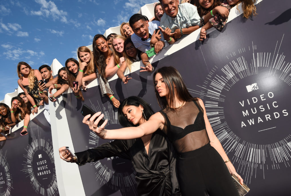 Kylie Jenner and Kendall Jenner take selfies at an awards show. Together, they have over 100 million Instagram followers.