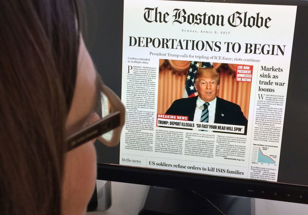 TOPSHOT - This April 10, 2016 photo taken in Washington before the outcome of the 2016 U.S. presidential election shows a woman reading an online version of a mockup of what a frontpage might look like if Donald Trump were declared the winner.