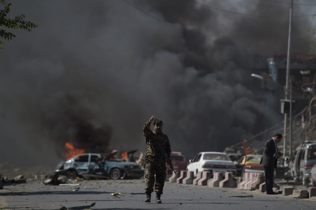 An Afghan security force member stands at the site of a car bomb attack in Kabul on May 31, 2017.