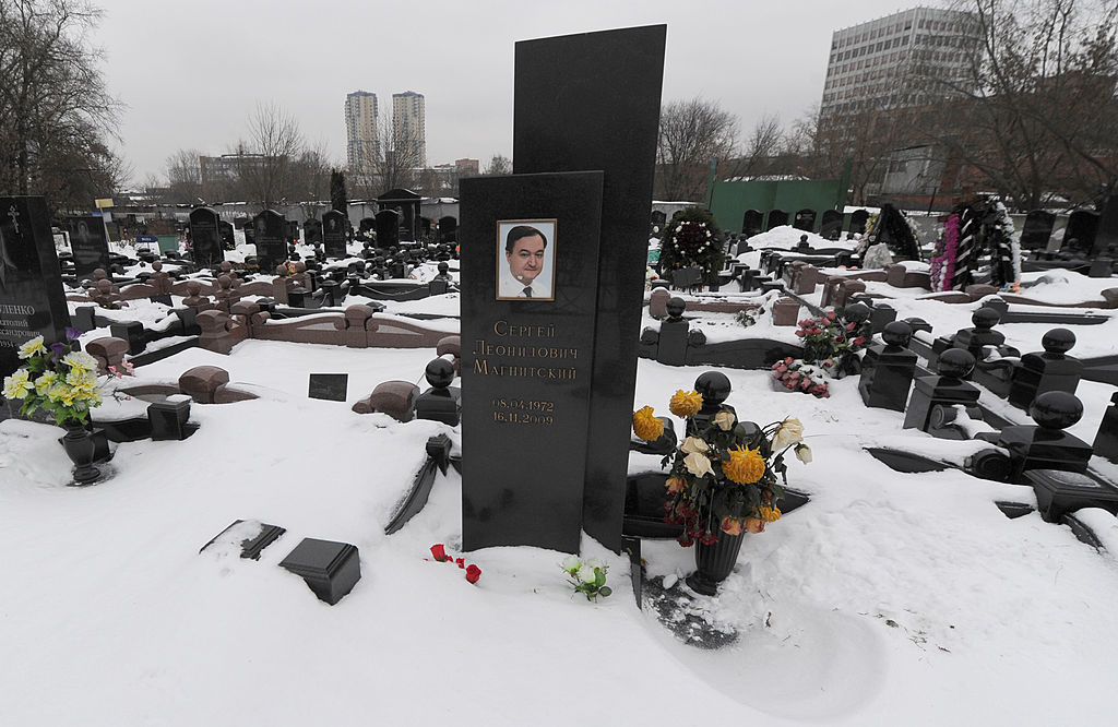A picture taken on December 7, 2012, shows  snow clad grave of Russian lawyer Sergei Magnitsky with his portrait on the tomb at the Preobrazhenskoye cemetery in Moscow.