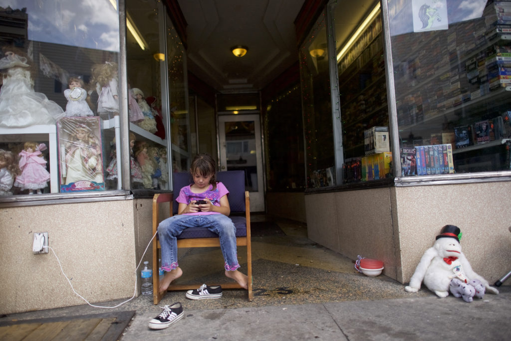 Alize Way-Heffner, 7, uses a smartphone on August 14, 2016 in Shenandoah, Pennsylvania.  The small Northeastern Pennsylvania town of 5,000 residents has a rich coal mining history.  The majority of nearby coal mines have closed and 20.1% of the population now exists below the poverty line, with a median household income of $18,714.
