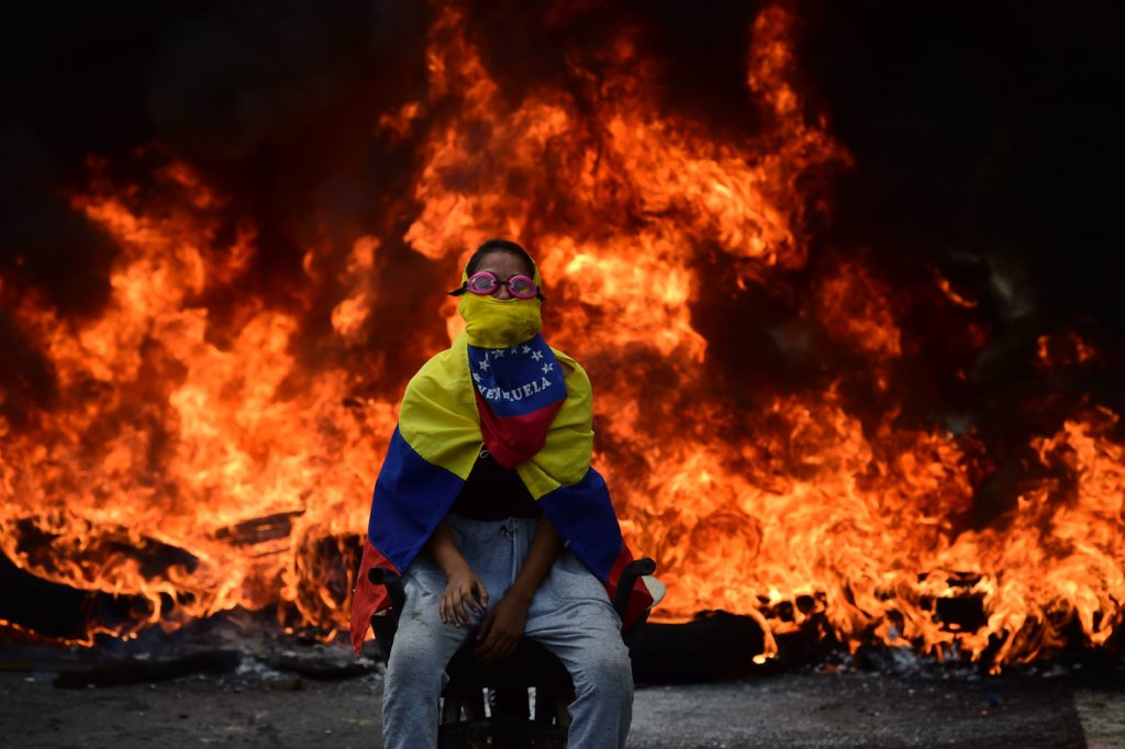 A Venezuelan opposition activist is backdropped by a burning barricade during a demonstration against President Nicolas Maduro in Caracas, on April 24, 2017. Protesters rallied on Monday vowing to block Venezuela's main roads to raise pressure on Maduro after three weeks of deadly unrest that have left 21 people dead. Riot police fired rubber bullets and tear gas to break up one of the first rallies in eastern Caracas early Monday while other groups were gathering elsewhere, the opposition said.