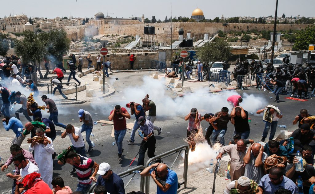 Palestinian worshippers run for cover from teargas fired by Israeli forces outside Jerusalem's Old City in front of the Al-Aqsa mosque compound, after Israeli police barred men under 50 from entering the Old City for Friday Muslim prayers as tensions rose and protests erupted over new security measures at the highly sensitive holy site on July 21, 2017.  The ban came after Israeli ministers decided not to order the removal of metal detectors erected at entrances to the Al-Aqsa mosque compound, known to Jews as the Temple Mount, following an attack nearby a week ago that killed two policemen.