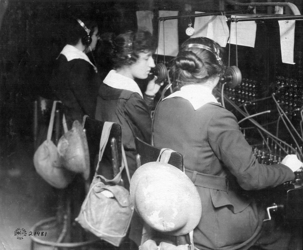 Only six women, working three at a time in 12-hour shifts, keep Pershing's headquarters connected with the rest of the Army during the Battle of St. Mihiel. Helmets and gas masks hang from their chairs. Left-to-right: Berthe Hunt, Tootsie Fresnel, Grace Banker.