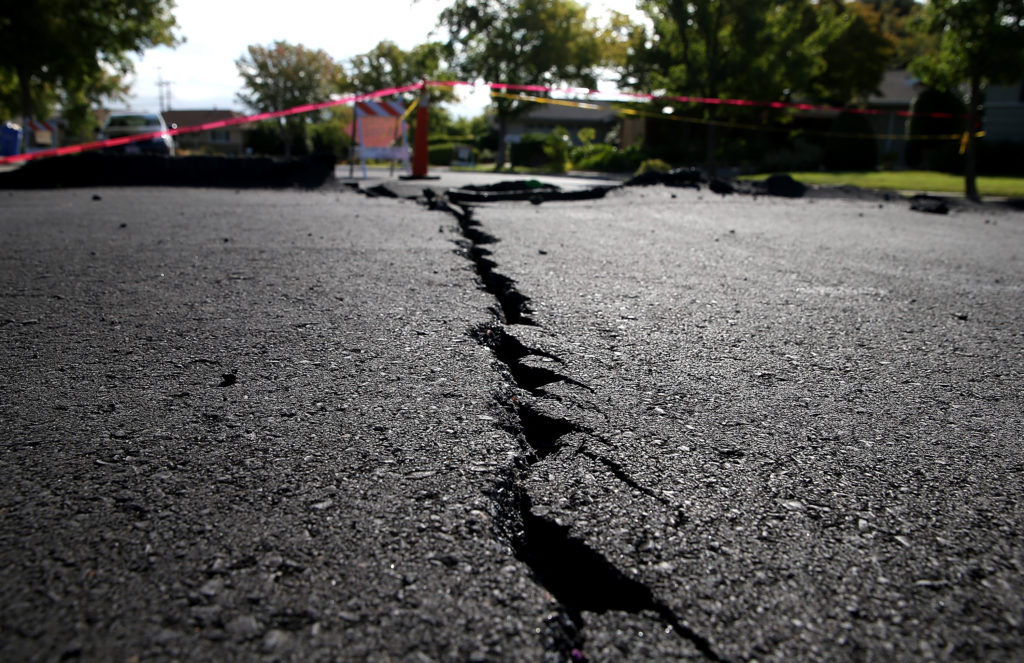 A crack runs down the center of an earthquake-damaged street on August 26, 2014 in Napa, California two days after a 6.0 earthquake rocked the Napa Valley.