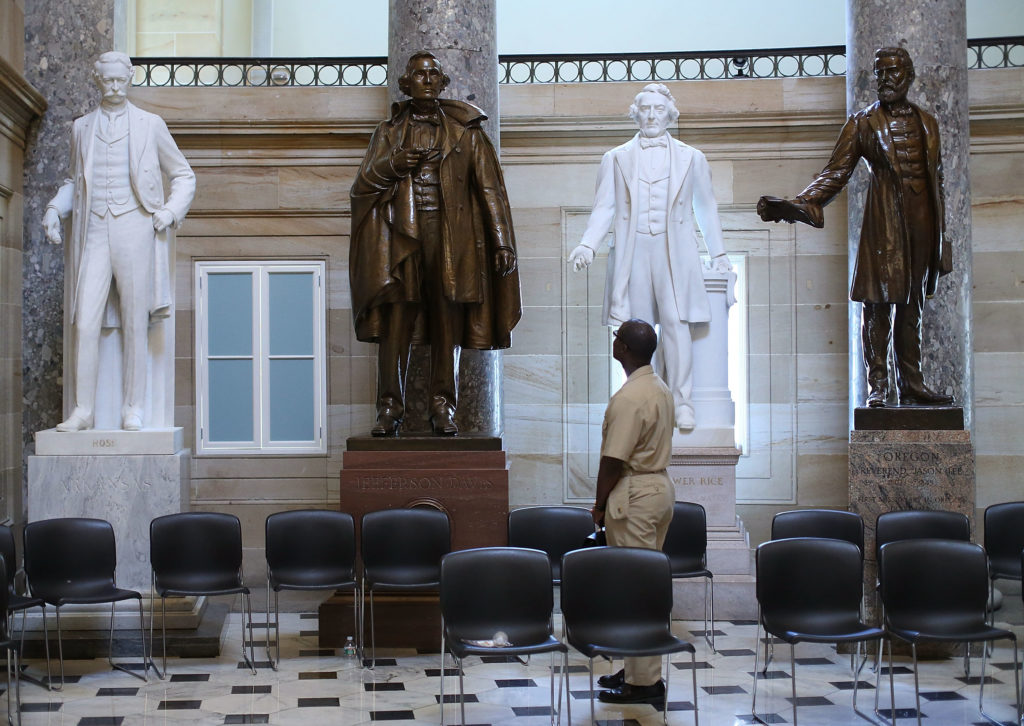 US Navy Lt. William Edmund Newsome looks at a bronze statue of Confederate president Jefferson Davis (2ndL) that stands inside of Statuary Hall at the US Capitol June 24, 2015 in Washington, DC. Some members of Congress are calling for the removal of the statue of the Confederate president from inside of the Capitol.