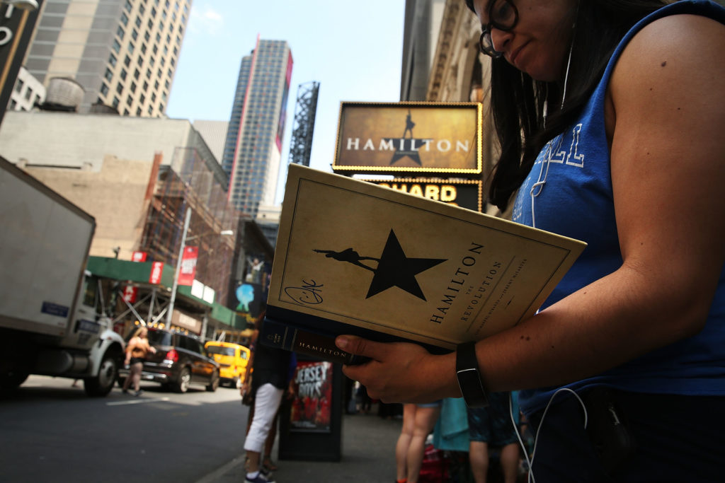 A woman displays her Hamilton autograph book outside of the the popular Broadway show Hamilton on June 21, 2016 in New York City. The Tony Award-winning Broadway hit has drawn huge crowds to the Richard Rogers theater in the hopes of getting increasingly scarce and expensive tickets. Carrying bed rolls, pillows and take-out food containers, many fans of the musical wait days in the heat and rain for a chance to get a cancellation ticket which are offered to the public once they're declined by members of the cast and crew.