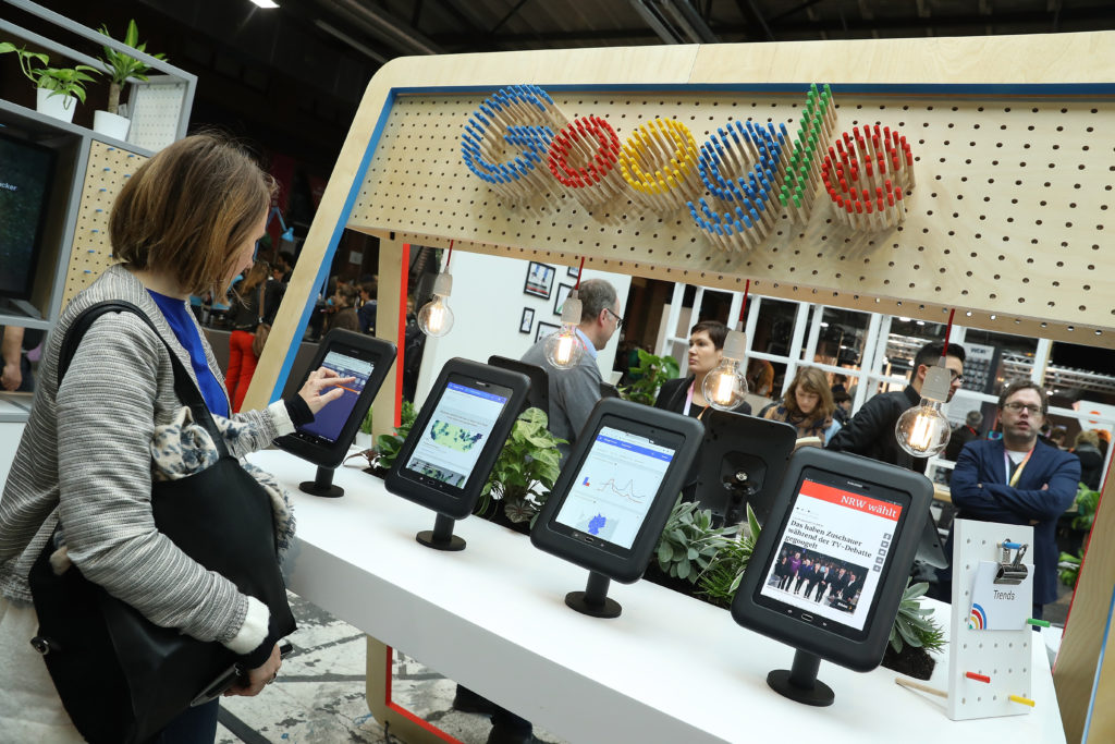 A visitor taps through news on a tablet at the Google Digitial News Initiative stand at the Re:publica 17 conference on digital society on May 8, 2017 in Berlin, Germany. The Re:publica, now in its 10th year, examines the confluence of digitial socety with media, government, entertainment, technology and culture.