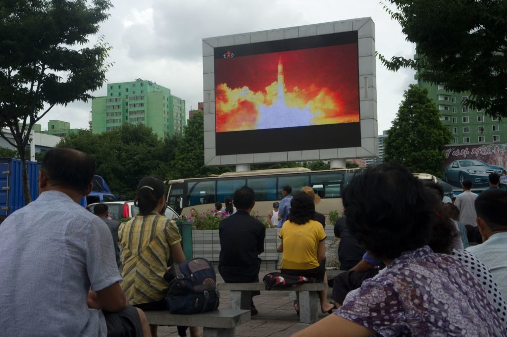 People watch as coverage of a missile test is displayed on a screen in a public square in Pyongyang on July 29, 2017.