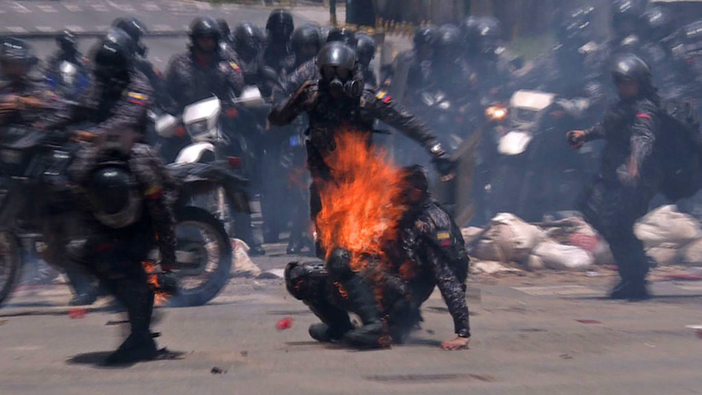 Police officers help a colleague who caught fire after an explosive device went off as they rode past during a protest against the elections for a Constituent Assembly in Caracas, Venezuela on July 30, 2017.