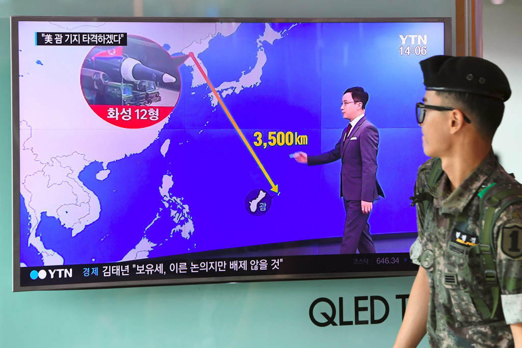 """A South Korean soldier walks past a television screen showing a graphic of the distance between North Korea and Guam at a railway station in Seoul on August 9, 2017. President Donald Trump issued an apocalyptic warning to North Korea on Tuesday, saying it faces """"fire and fury"""" over its missile program, after U.S. media reported Pyongyang has successfully miniaturized a nuclear warhead."""