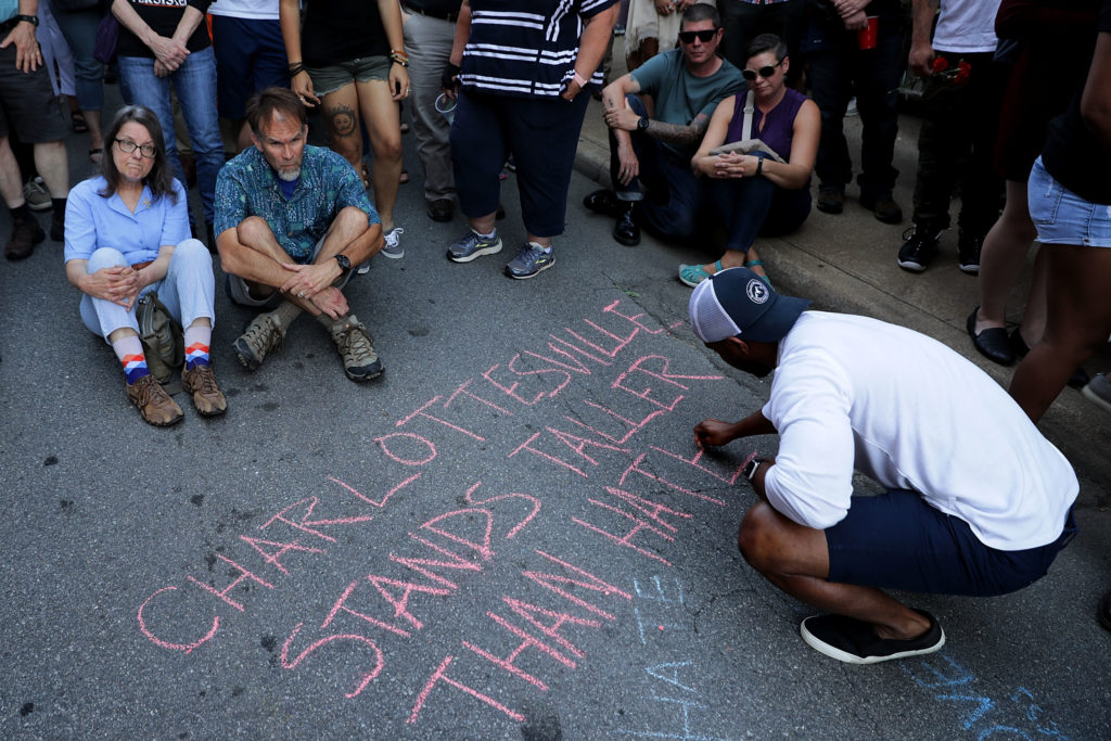Hundreds of people gather for a vigil on the spot where 32-year-old Heather Heyer was killed when a car plowed into a crowd of people protesting against the white supremacist Unite the Right rally August 13, 2017 in Charlottesville, Virginia. Charlottesville is calm the day after violence errupted around the Unite the Right rally, a gathering of white nationalists, neo-Nazis, the Ku Klux Klan and members of the 'alt-right,' that left Heyer dead and injured 19 others.