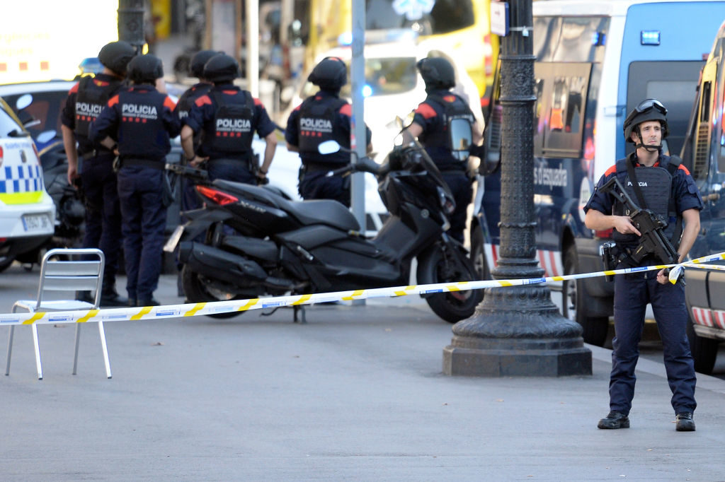 Armed policemen stand in a cordoned off area after a van ploughed into the crowd, injuring several persons on the Rambla in Barcelona.