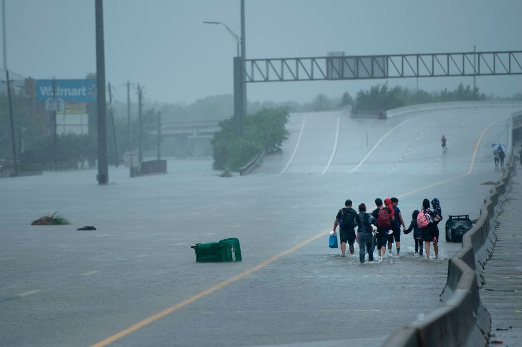 Evacuation residents from the Meyerland area walk onto an I-610 overpass for further help during the aftermath of Hurricane Harvey in Houston, Texas.