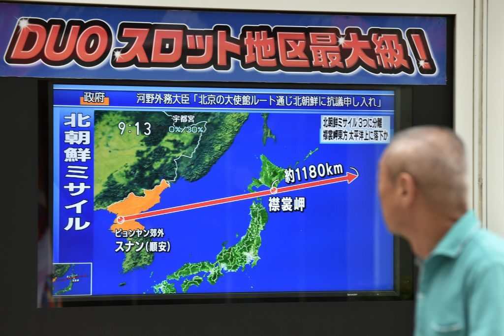 A pedestrian looks at a television screen displaying a map of Japan (R) and the Korean Peninsula in Tokyo on August 29, following a North Korean missile test that passed over Japan.