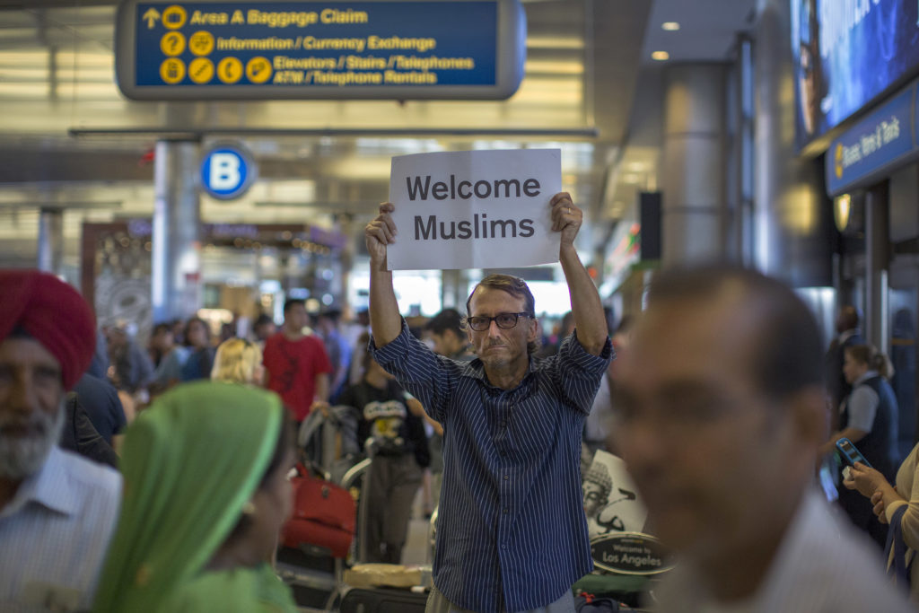 John Wider carries a welcome sign near arriving Sikh travelers at Los Angeles International Airport (LAX) on June 29, 2017.