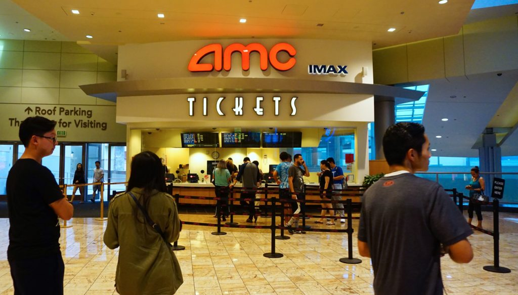 "Movie goers purchase tickets at an AMC movie theater in Arcadia, California on August 2, 2017.  AMC Entertainment Holdings, the world's largest movie theater owner, announced a ""shocking"" expectation for second-quarter losses, with stocks diving by 25 percent August 2nd amid a weak box office."