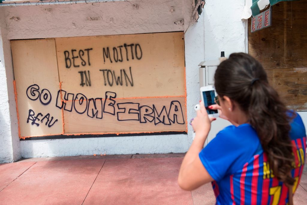 A woman takes a photo of a message on a boarded up window at a restaurant in advance of Hurricane Irma in Miami Beach, Florida.