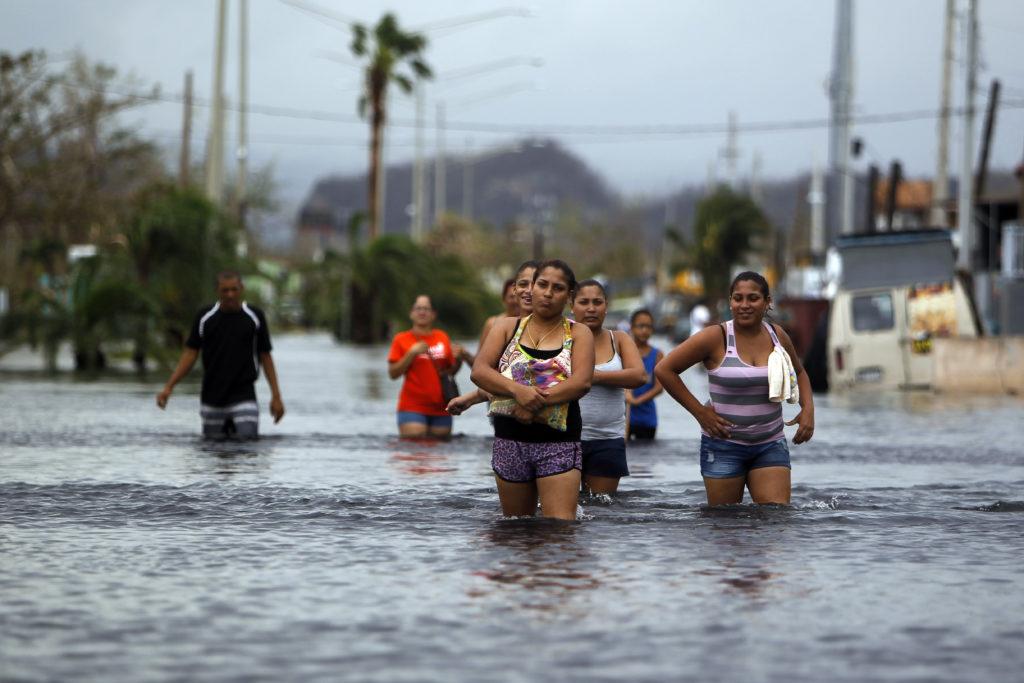 People walk on a flooded street in the aftermath of Hurricane Maria in San Juan, Puerto Rico on September 22, 2017. Puerto Rico battled dangerous floods after Hurricane Maria ravaged the island, as rescuers raced against time to reach residents trapped in their homes and the death toll climbed. Puerto Rico Governor Ricardo Rossello called Maria the most devastating storm in a century after it destroyed the US territory's electricity and telecommunications infrastructure.