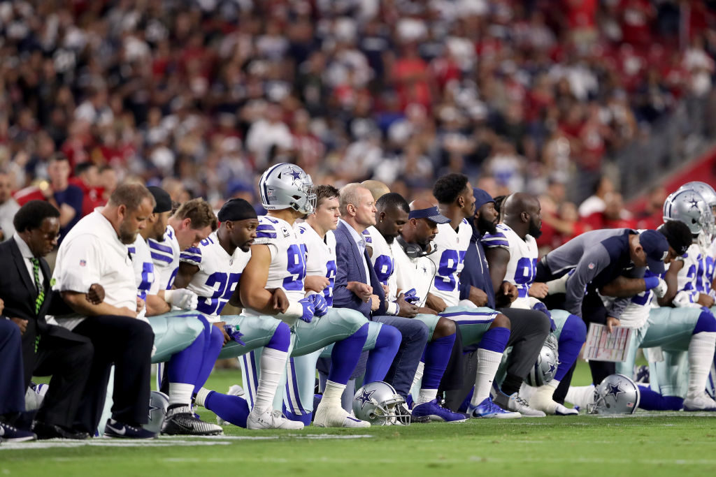Members of the Dallas Cowboys link arms and kneel before the National Anthem ahead of the start of a game against the Arizona Cardinals.