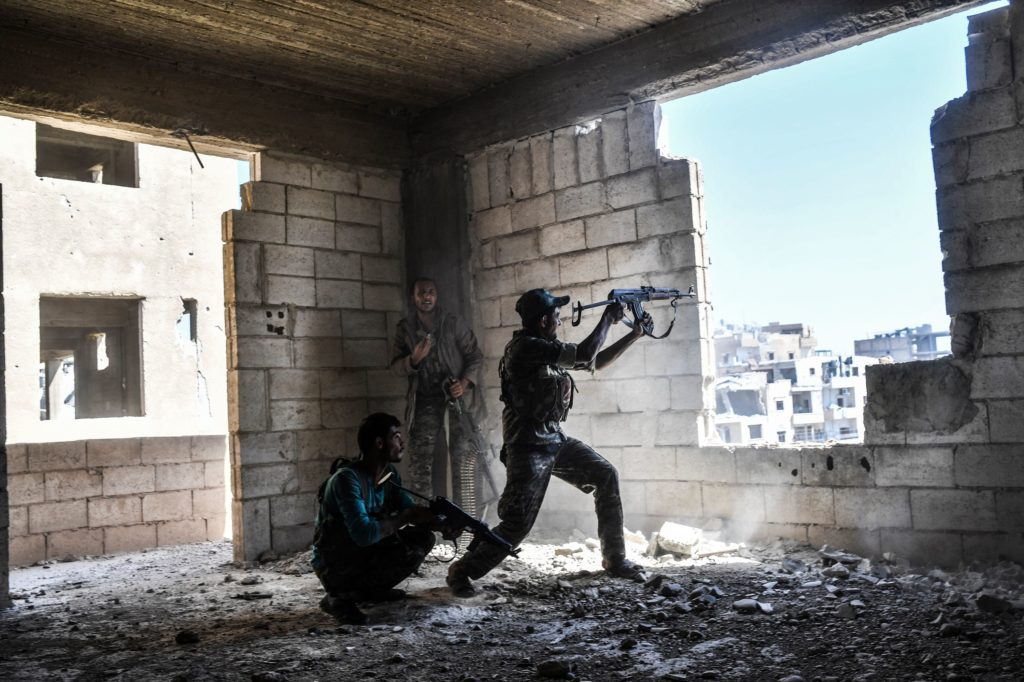 Members of the Syrian Democratic Forces fire their arms during a battle against Islamic State (IS) group jihadists to retake the central hospital of Raqa on the western frontline of the city on September 28, 2017.  Syrian fighters backed by US special forces are battling to clear the last remaining Islamic State group jihadists holed up in their crumbling stronghold of Raqa.