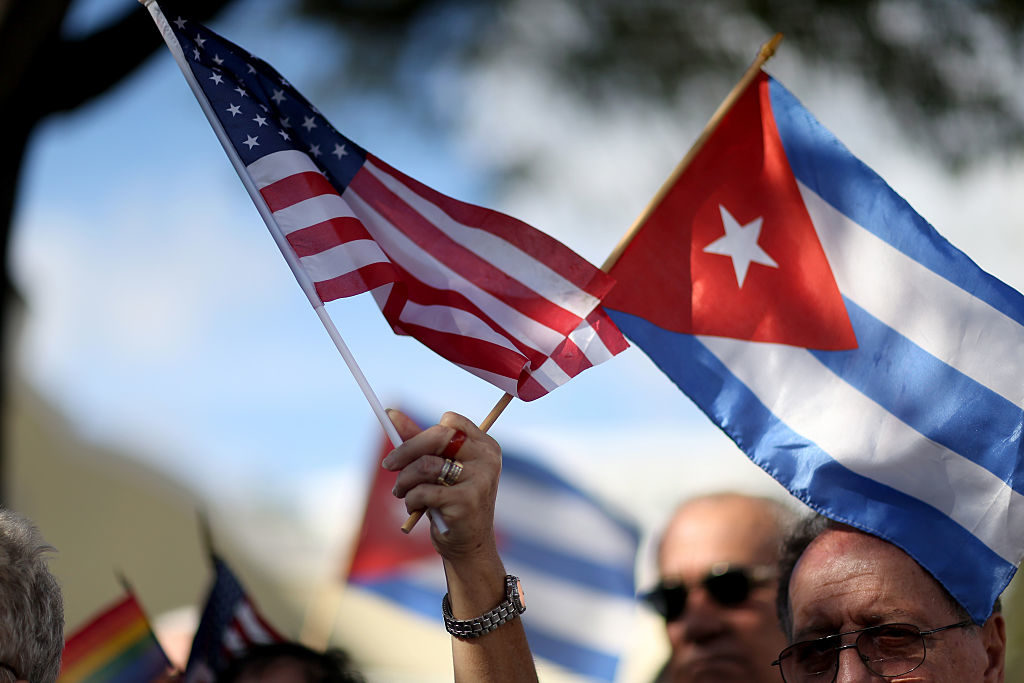 A protester holds flags in opposition of President Barack Obama's 2014 announcement earlier of a change to the United States' Cuba policy.