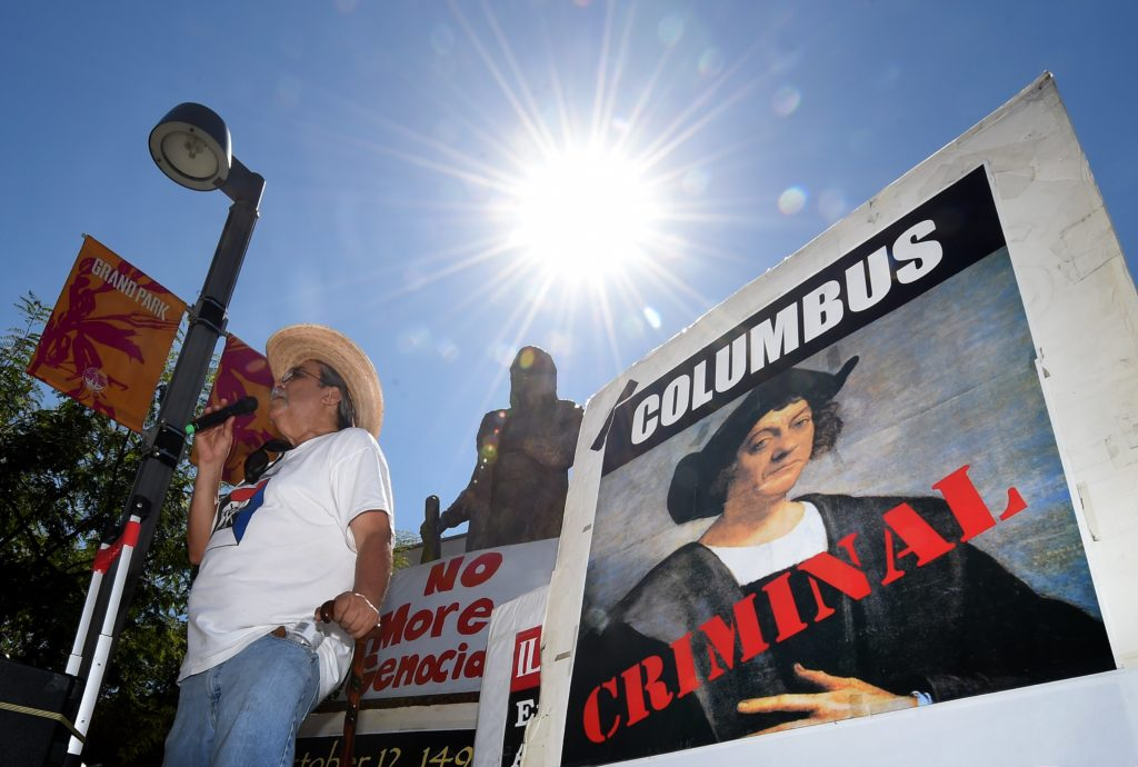 Olin Tezcatlipoca from the Mexica Movement speaks to demonstrators in front of a statue of Christopher Columbus during a protest against Columbus Day in Grand Park, Los Angeles, California on October 11, 2015.  The Mexica Movement is amongst a growing group of people and US cities that want change the name of the 'Columbus Day' holiday to 'Indigenous Peoples Day.'