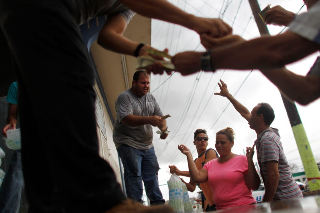 People buy ice at a local ice plant in the aftermath of Hurricane Maria, in Arecibo, Puerto Rico, September 30, 2017. US military and emergency relief teams ramped up their aid efforts for Puerto Rico amid growing criticism of the response to the hurricanes which ripped through the Caribbean island.