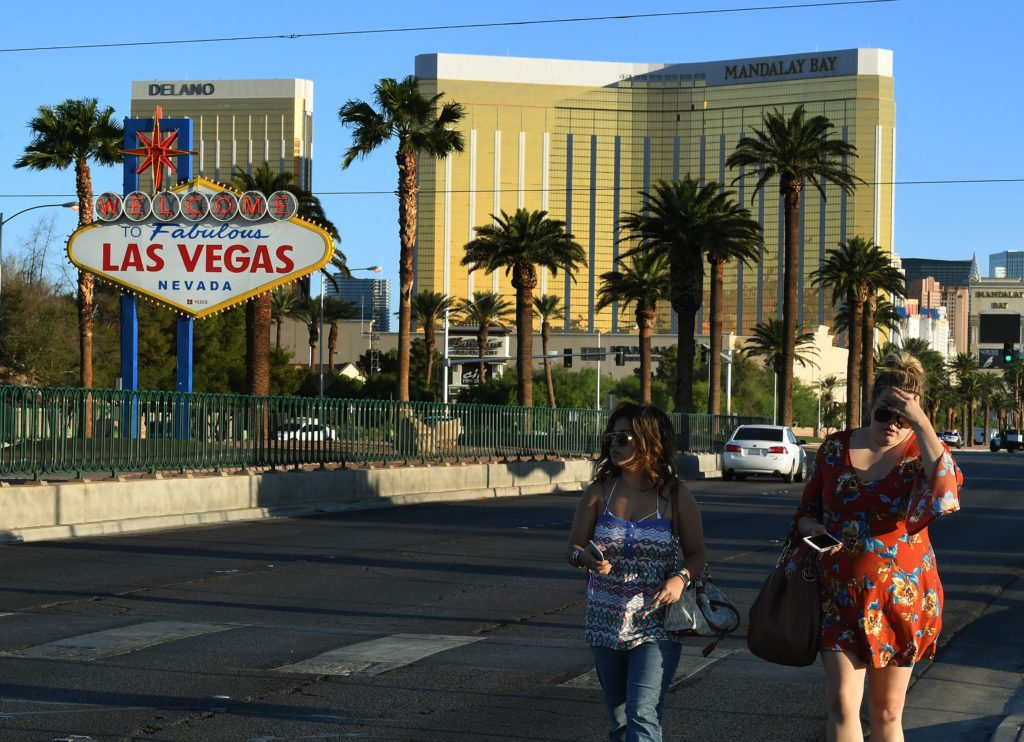 Two festivalgoers leave the area around the Mandalay Hotel after a gunman killed more than 50 people and wounded more than 500 others when he opened fire on a country music concert in Las Vegas, Nevada on October 2, 2017.  Police said the gunman, a 64-year-old local resident named as Stephen Paddock, had been killed after a SWAT team responded to reports of multiple gunfire from the 32nd floor of the Mandalay Bay, a hotel-casino next to the concert venue.