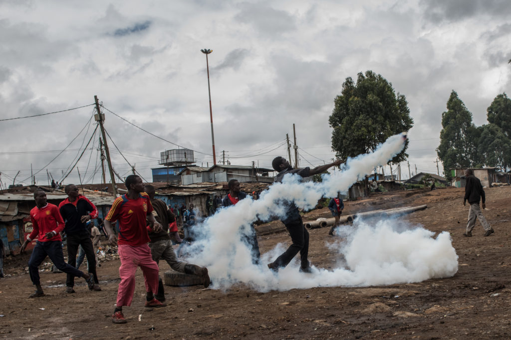A National Super Alliance (NASA) protester throws a tear gas canister back at police in the Kibera slum on October 26, 2017 in Nairobi, Kenya. Protestors in Kibera have boycotted the vote and are attempting to block polls during Kenya's controversial rerun election.
