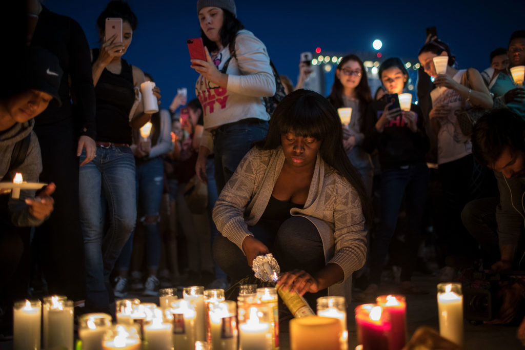 Mourners light candles during a vigil at the corner of Sahara Ave. and Las Vegas Blvd. for the victims of the mass shooting Oct. 2, 2017, in Las Vegas. Late Sunday night, a lone gunman killed 58 people and injured nearly 500 after he opened fire on a crowd at a country music festival. The massacre is one of the deadliest mass shootings in U.S. history.