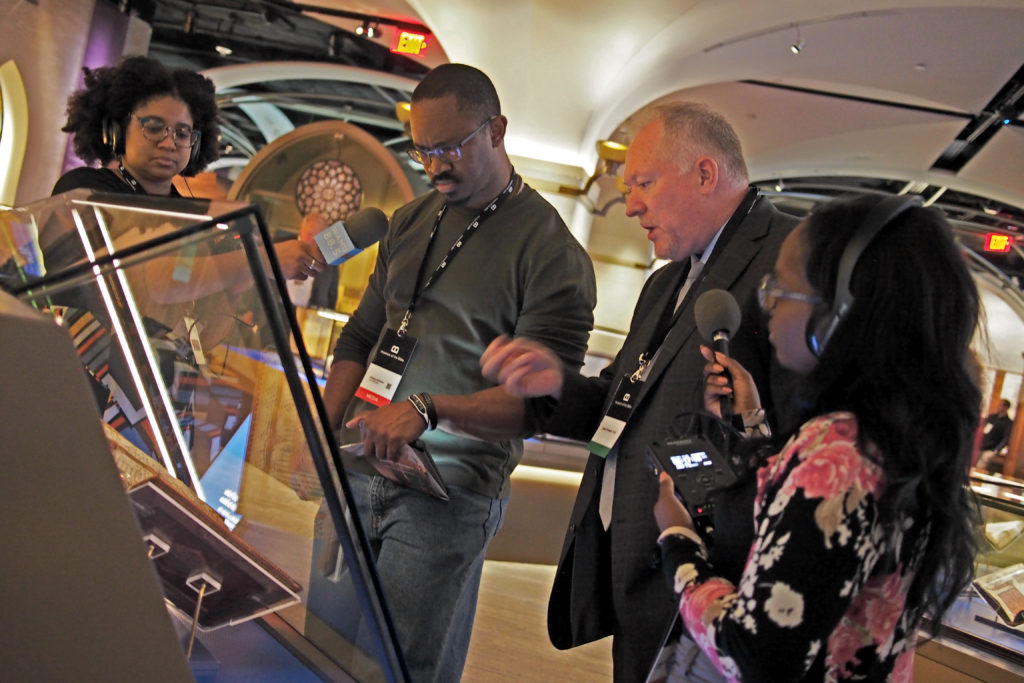 Museum of the Bible Director of Collections David Trobisch shows Joshua early religious texts written on papyrus as producers Lindsay Foster Thomas (L) and Jonquilyn Hill (R) record the conversation.
