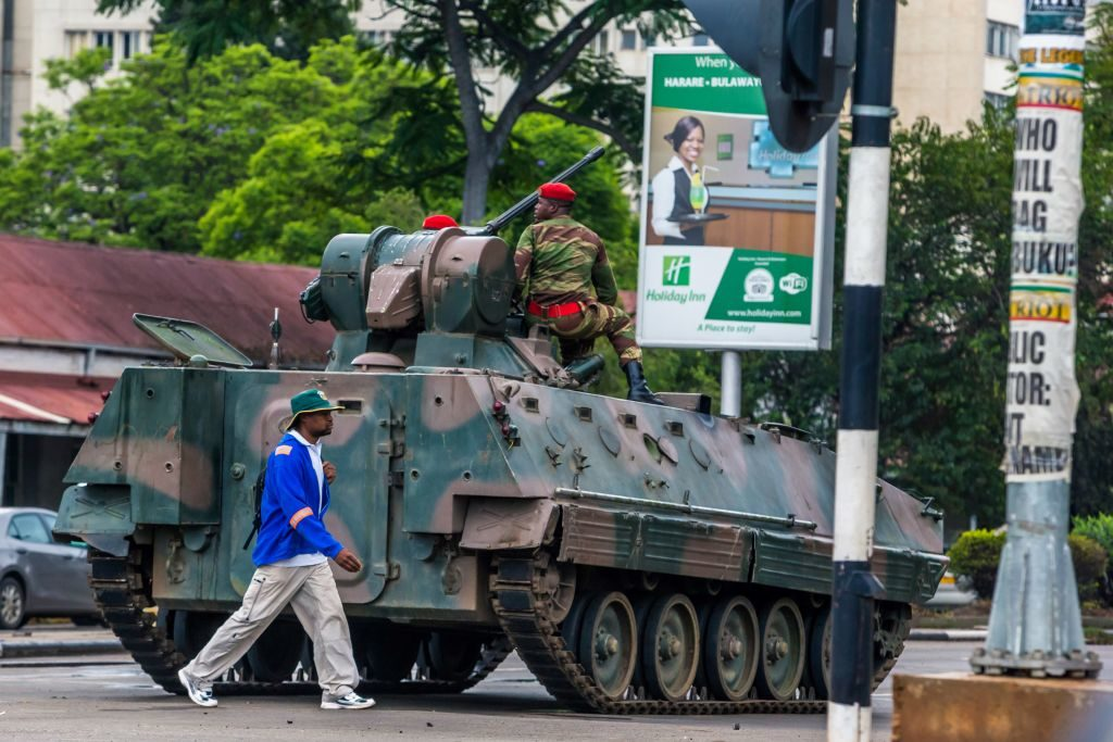 A man walks past an armoured personnel carrier that stations by an intersection as Zimbabwean soldiers regulate traffic in Harare.