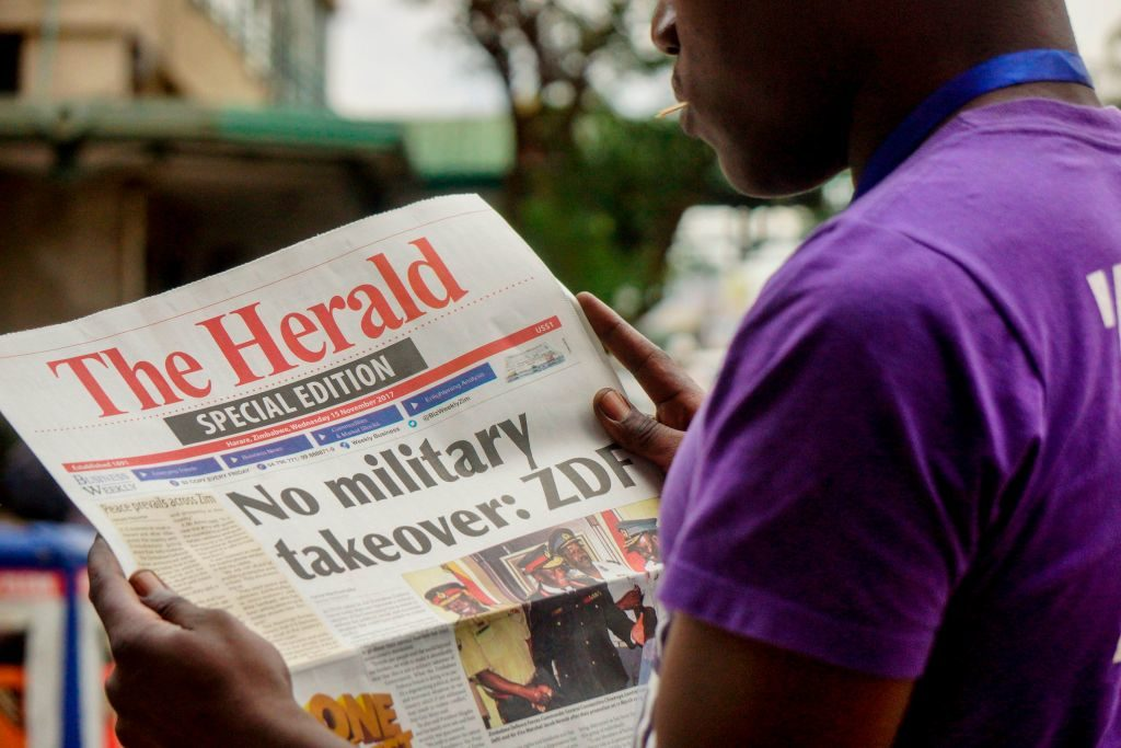 A man reads the front page of a special edition of The Herald newspaper about the crisis in Zimbabwe with the headline 'No military takeover.